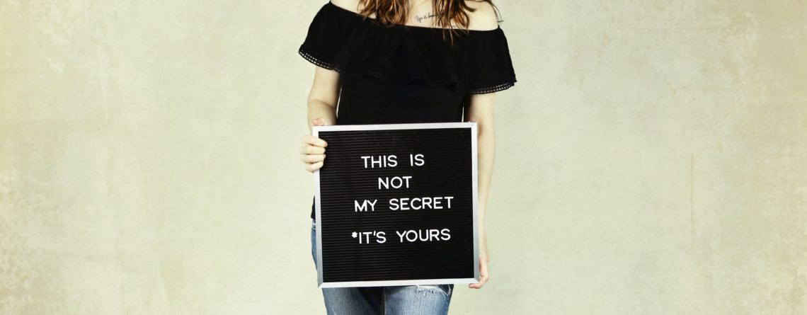 Woman holding a board with the words, this is not my secret, its yours.